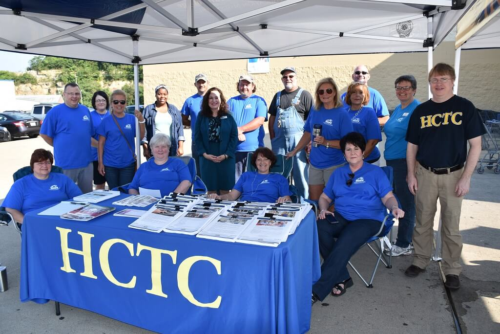 hctc employees at a table smiling outside