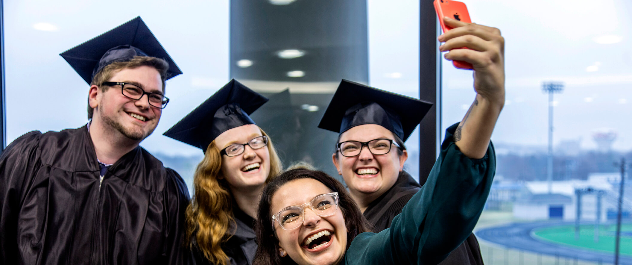 Three graduates and a friend taking a selfie on a cell phone