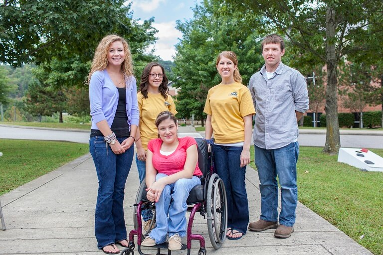 Four students posing with a student in a wheelchair