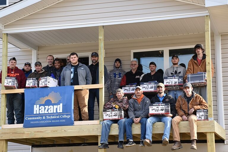 construction students outside of house with Hazard banner